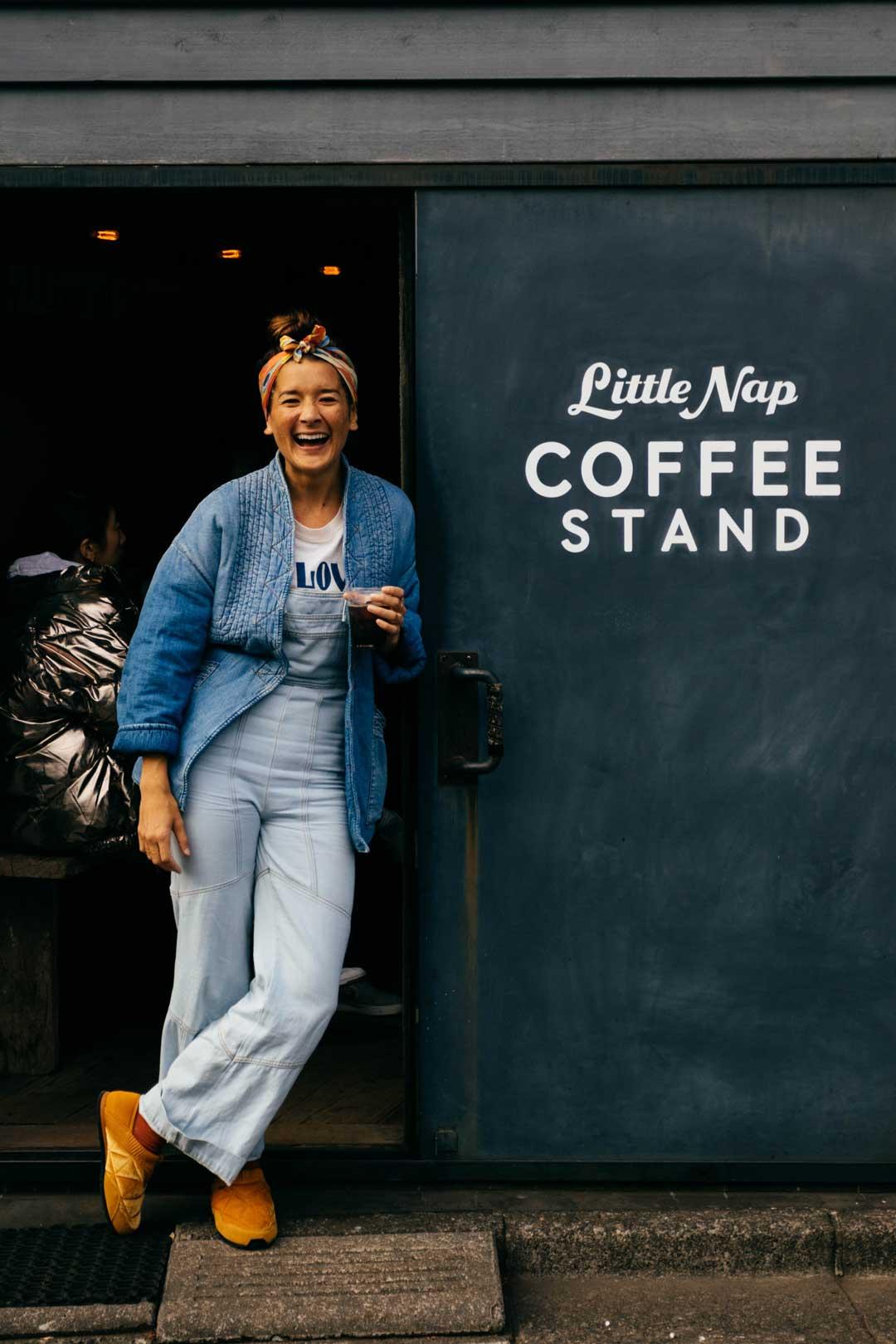 Tara Michie next to coffee sign in Japan.