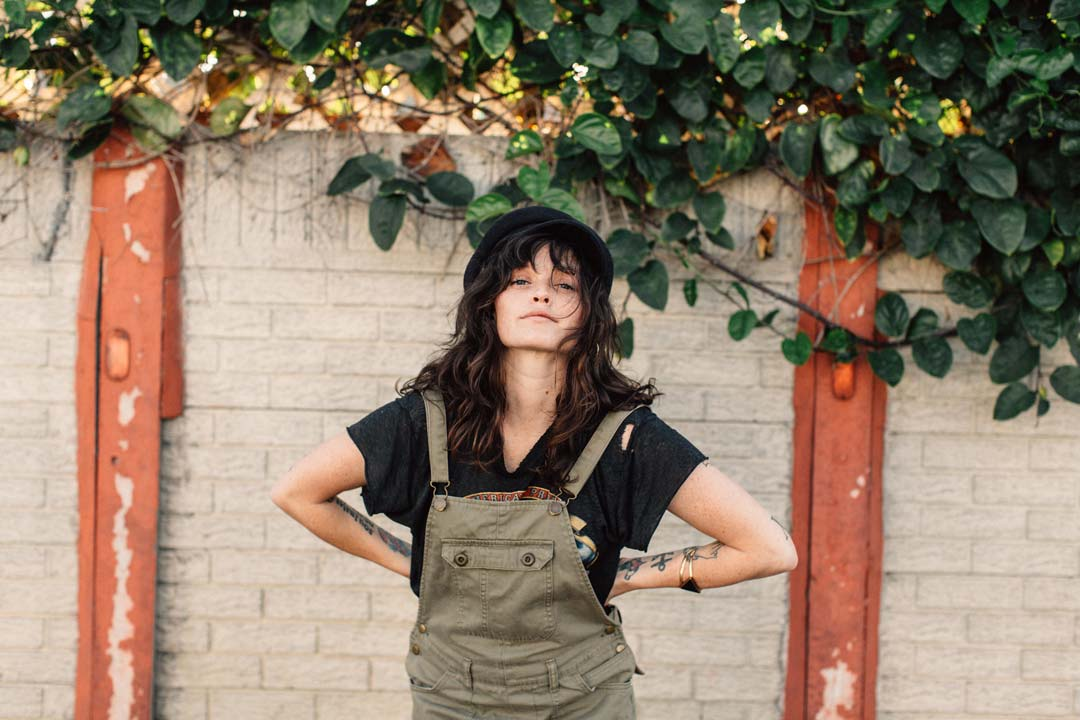 Lindsay Perry poses in front of a while brick wall wearing overalls.