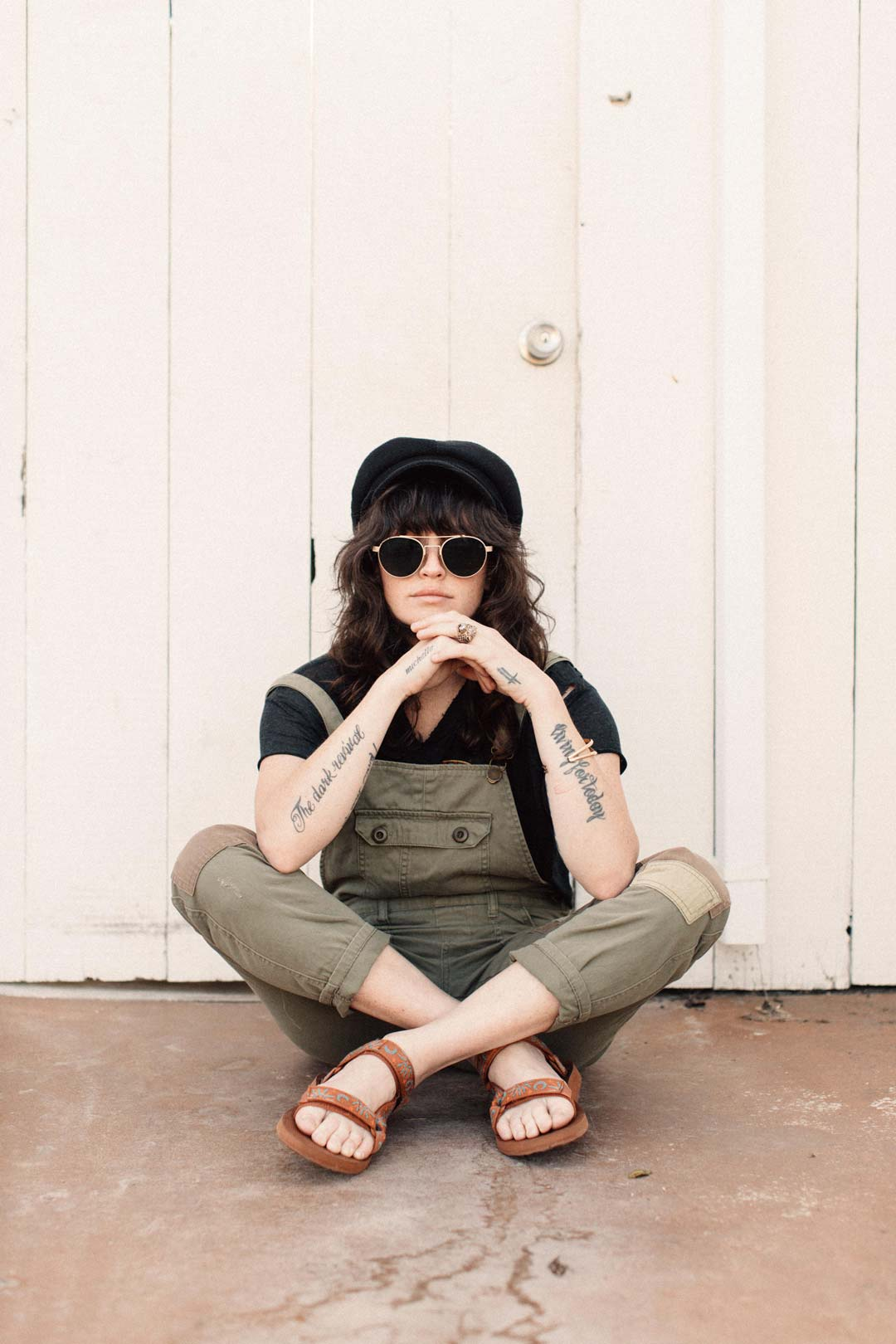 Lindsay Perry sits in front of a white wall wearing sunglasses, overalls and Sun and Moon Original Universal sandals.