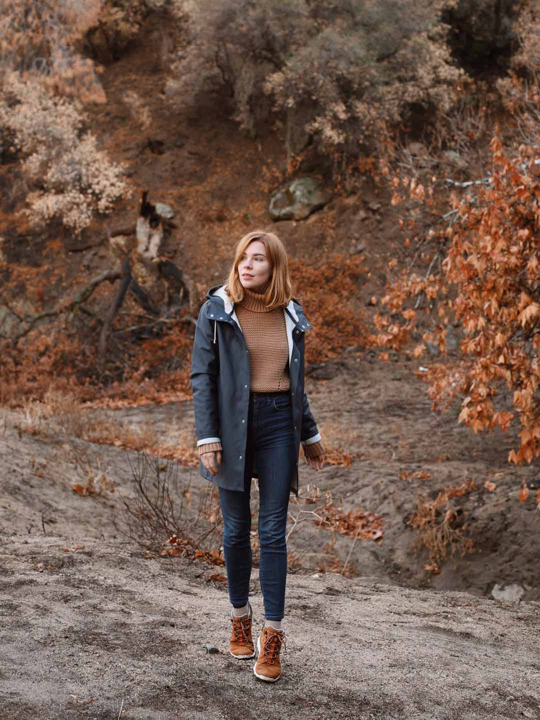 Courtney Halverson walks in the woods wearing the Women's Arrowood Lux Mid sneakerboots.