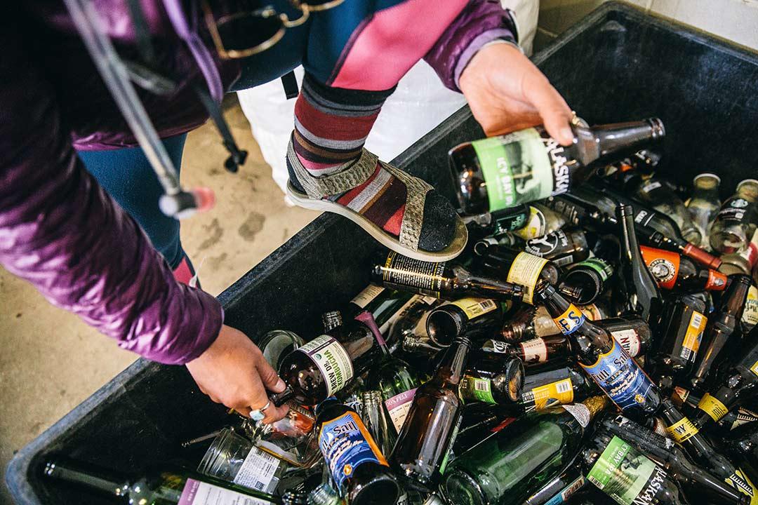 Mariah Reading searches through bottles at a sorting center wearing  Teva sandals.